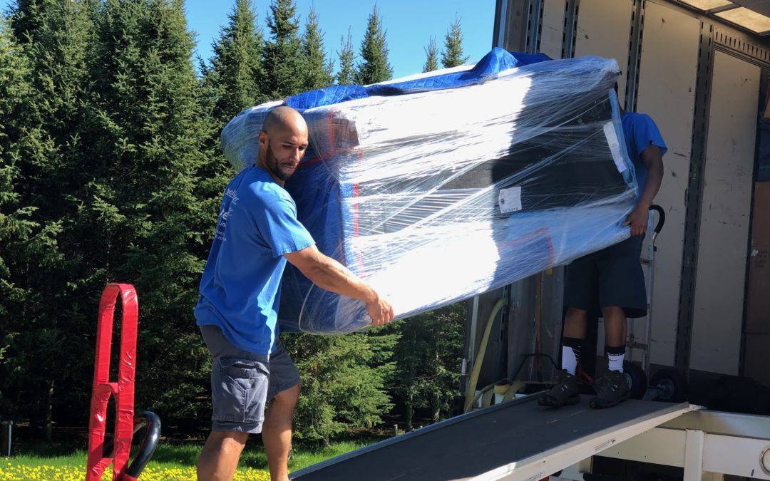 Full-service movers moving items into moving truck.